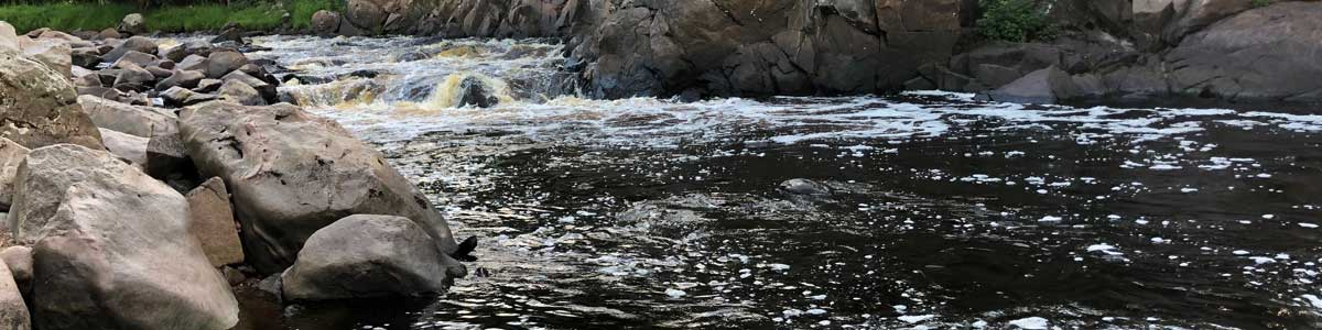 Brown water flowing over large rocks at Big Falls County Park