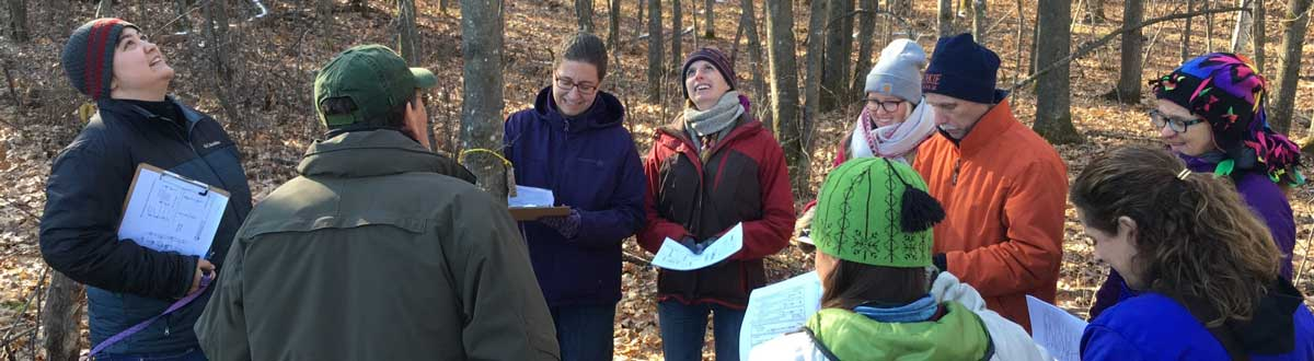 Master Naturalist Instructors learning about winter tree identification in the woods