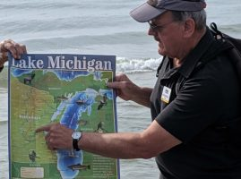 Master Naturalist instructor points to map of Wisconsin with Lake Michigan in background