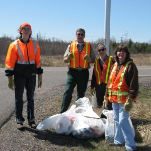 people wearing safety vests during roadside clean-up