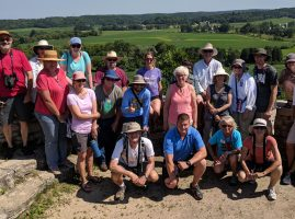 Image of Master Naturalists posed for a group picture during field trip on a sunny day. Farm fields and rolling hills appear in behind them.