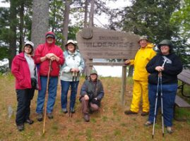 Master Naturalists pose during hike with walking sticks in the rain